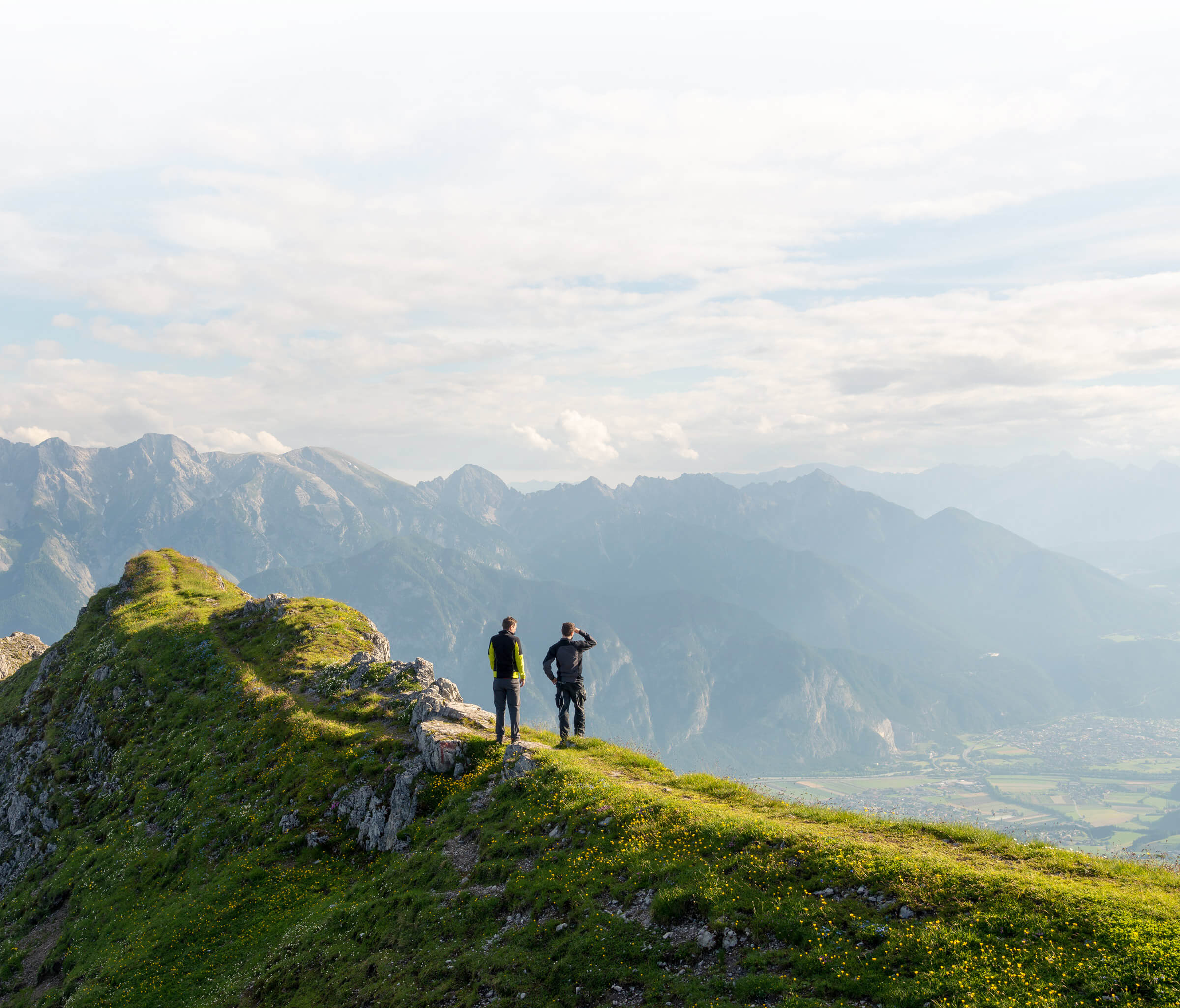 Summer scene. Two men on top of a mountain.