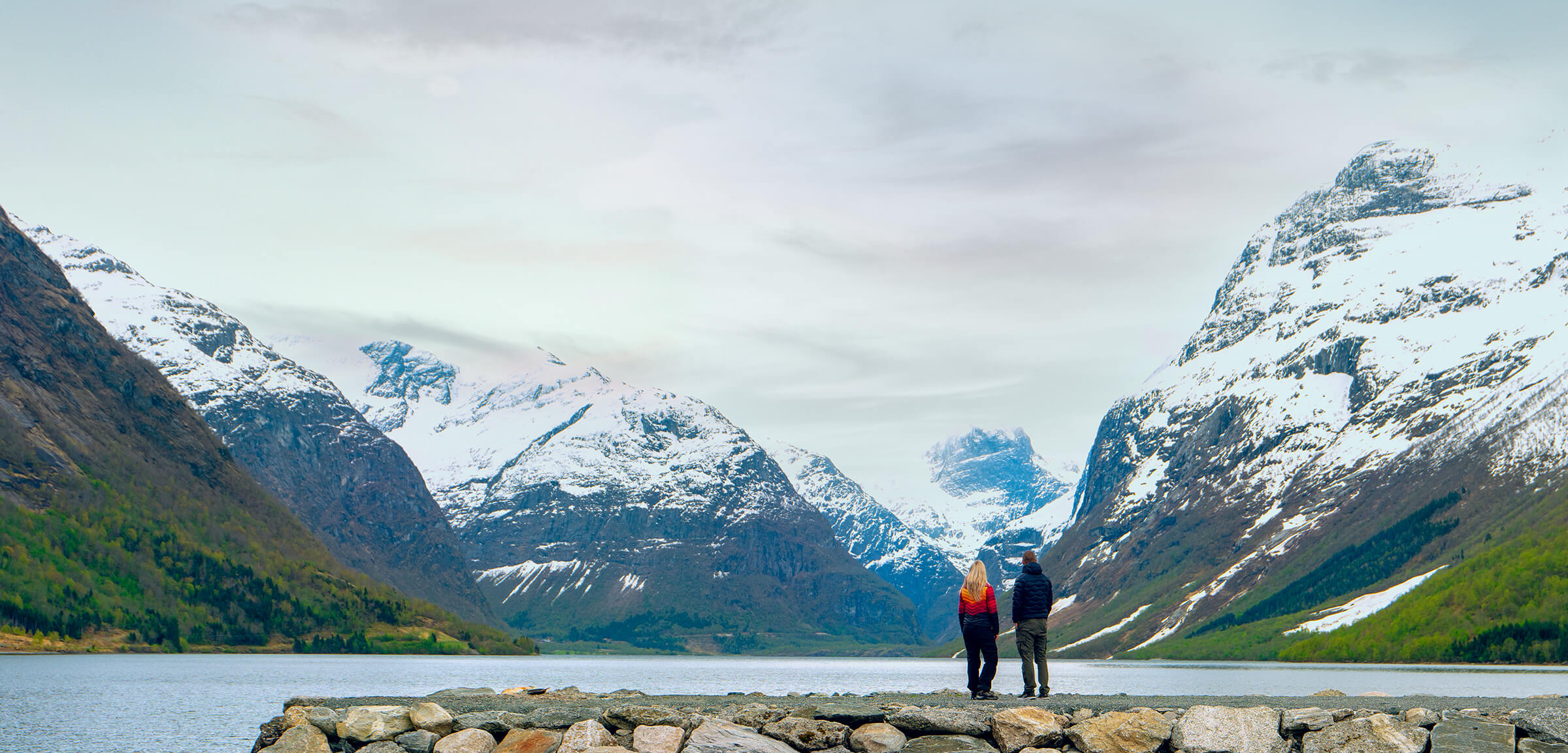 Two people on a stone bridge looking at mountains